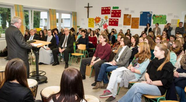 Schulleiter Willi Kruse begrüßt die Schüler und die Lehrer zu der Verlehung der Urkunde in der Musikaula. Foto: SMMP/Bock